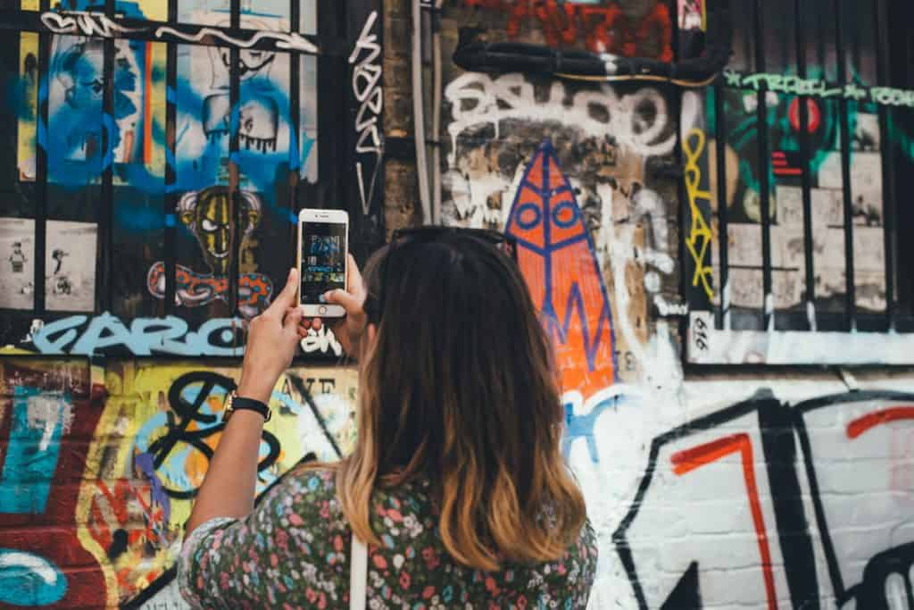 Girl takes photo of graffiti on her phone